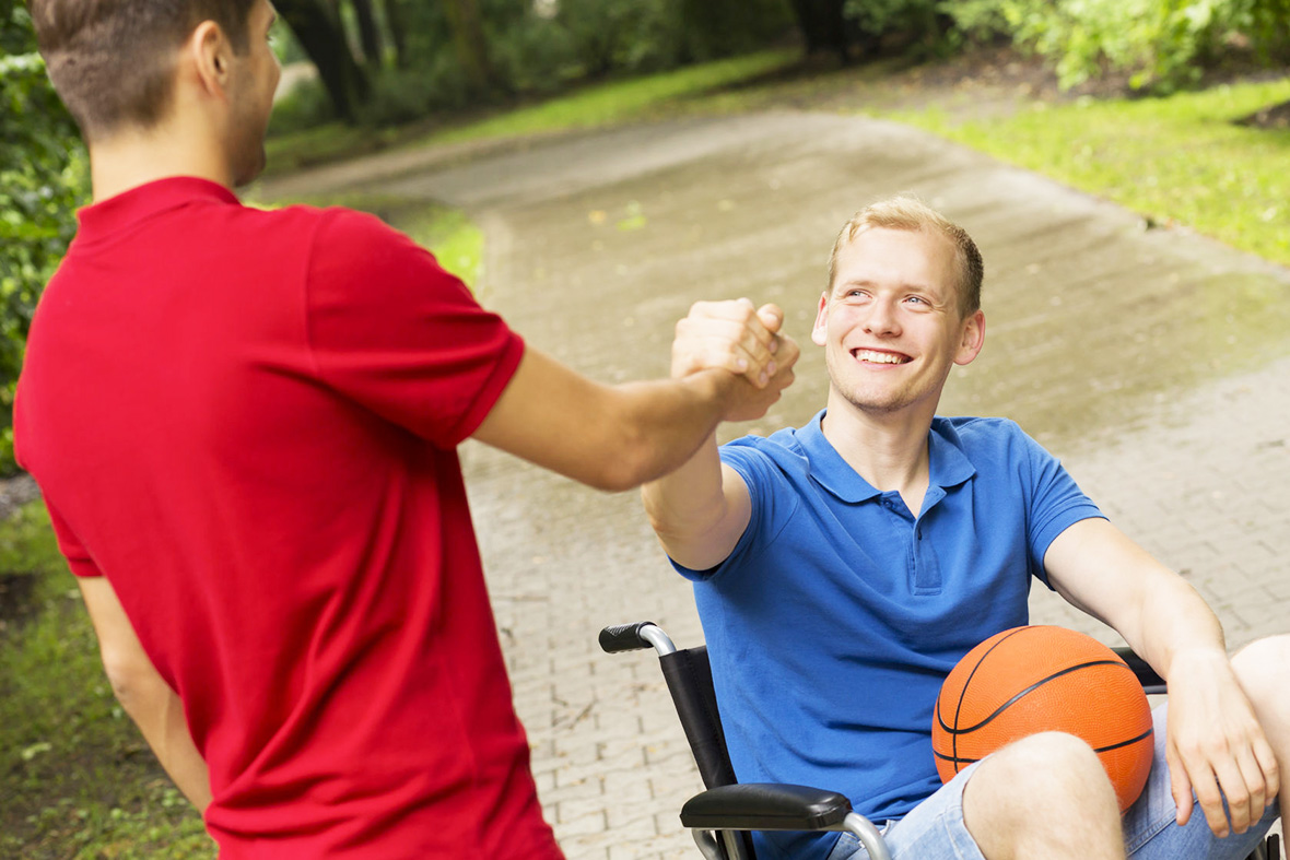 63927960 - shot of a young man in a wheelchair smiling at his friend in a park
